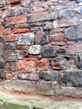 The criss-crossed part of the wall are bricks taken from Hadrians Wall
